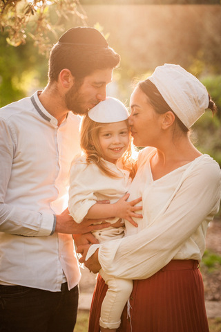 צילומי משפחות - הורים מנשקים את בנם